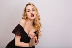 Closeup portrait of sexy blonde girl with sensual lips, passionate young woman with curly hairstyle, beckoning finger. Posing in studio with white background royalty free stock photography