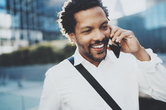 Closeup portrait of smiling American African man using smartphone to call friends at sunny street.Concept of happy young Stock Photography
