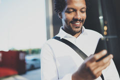 Closeup portrait of smiling American African man using smartphone to text message friends at sunny street.Concept of. Happy young handsome people enjoying Royalty Free Stock Photography