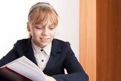 Closeup portrait of smiling blond Caucasian schoolgirl reading t Stock Photography