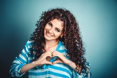 Woman making heart sign with hands. Closeup portrait smiling cheerful happy young curly girl woman making heart sign with hands isolated on blue wall background royalty free stock photo
