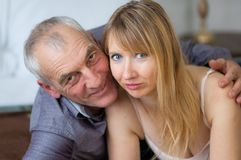 Closeup Portrait of Smiling Couple with Age Difference. Beautiful Young Woman with Her Senior Lover Lying on the Bed. Closeup Portrait of Smiling Couple with Royalty Free Stock Photography