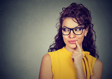 Closeup portrait of a smiling flirting woman in yellow dress with finger on lips looking sideways royalty free stock photo