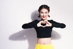 Closeup portrait smiling happy young woman making heart sign, sy Stock Image