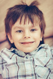 Closeup portrait of smiling little boy with brown eyes. Wearing checkered shirt lying on floor and looking at camera. Happy childhood concept, selective focus royalty free stock photos