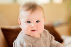 Closeup portrait of smiling little child with blond hair and blue eyes wearing knitted sweater sitting on sofa stock photos