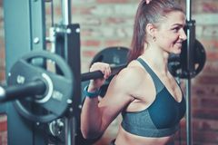 Closeup portrait smilling athletic woman exercising with barbell at smith machine. Closeup portrait smilling athletic woman exercising with barbell at smith royalty free stock photography