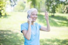 Closeup portrait of sporty senior lady on phone call stock photos