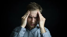 Closeup portrait of stressed man with headache, isolated on black background