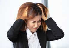 Closeup portrait stressed, Young Asian businesswoman stressed is going crazy pulling her hair in frustration at office royalty free stock photos