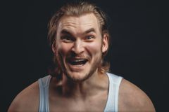 Closeup portrait of strong guy with stupid face isolated black background. Funny look. madness concept stock images