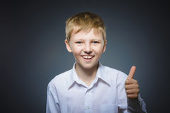 Closeup portrait successful happy boy show thumb up isolated grey background. royalty free stock image