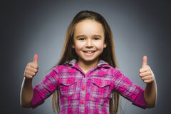 Closeup portrait successful happy girl show thumb up grey background. royalty free stock photography