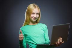 Closeup portrait successful happy girl show thumb up and using laptop isolated grey background Royalty Free Stock Image
