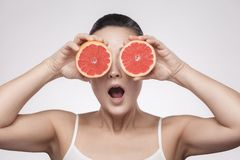 Closeup portrait of suprized woman with perfect skin smiling after cream, balm, mask, lotion, holding half of grapefruit and stock images