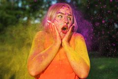 Closeup portrait of surprised blonde model having fun in a cloud of yellow and purple dry Holi paint stock photo