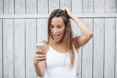 Closeup portrait surprised young girl looking at phone seeing news or photos Stock Photography