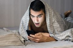 Closeup portrait of surprised young man messaging on smart phone in bed at home in the morning . the concept-social networking, te. Chnology, Internet Stock Image