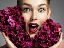 Closeup portrait of a surprised young woman. Female face with bright vivd makeup. Emotional girl with purple fowers stock photography