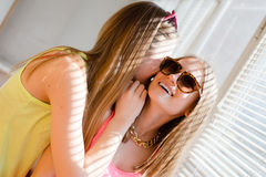 Closeup portrait of talking secrets 2 beautiful blond young women having fun happy smiling on sunny windows background Royalty Free Stock Image