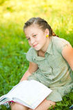 Closeup portrait of teen girl on a grass with book Royalty Free Stock Images