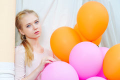 Closeup portrait of tender young woman with balloons. Closeup portrait of beautiful teenager model posing with bright and colorful balloons stock image
