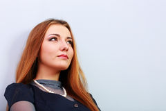 Closeup portrait of a thoughtful redhead woman. On gray background royalty free stock photos