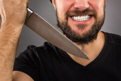Closeup portrait of a threatening man with beard holding a knife Royalty Free Stock Photography