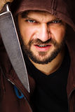 Closeup portrait of a threatening man with beard holding a knife. In his hands over gray background Royalty Free Stock Photos
