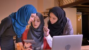 Closeup portrait of three young cheerful muslim businesswomen in hijabs having a lively conversation comparing a subject stock video