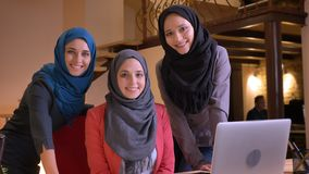 Closeup portrait of three young muslim female office workers in hijabs looking straight at camera and smiling being in stock footage