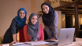 Closeup portrait of three young muslim female office workers in hijabs looking straight at camera and smiling happily on stock video