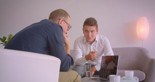 Closeup portrait of two adult caucasian businessmen having a discussion using laptop sitting in armchairs in office. Indoors stock video footage