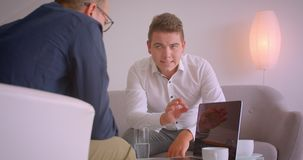 Closeup portrait of two attractive adult caucasian businessmen having a discussion using laptop sitting in armchairs in. Office indoors stock footage