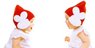 Closeup portrait two baby twins in red hats sitting face to face Royalty Free Stock Images