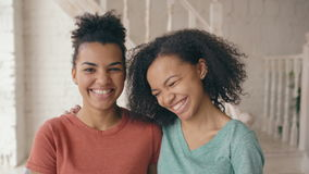 Closeup portrait of two beautiful african american girls laughing and looking into camera. Women show emotions from stock footage