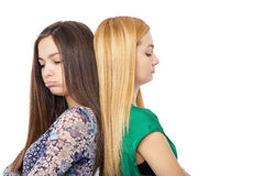 Closeup portrait of two bored teenage girls standing back to bac Stock Images