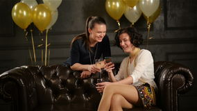 Closeup Portrait of Two Brunettes in Short Dresses with Glasses of Champagne in Hands During a Party. Ladies are Using. Smartphone and Smiling, HD stock footage