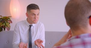Closeup portrait of two caucasian businessmen having a meeting discussion indoors in office. Young man getting annoyed. And frustrated stock footage