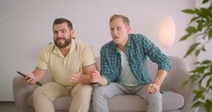 Closeup portrait of two caucasian male friends watching sports on TV and celebrating together sitting on couch at home