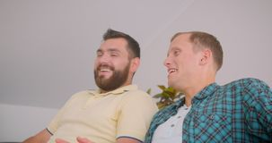 Closeup portrait of two caucasian men watching a comedy on TV together laughing happily sitting on couch at home indoors.  stock video footage