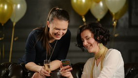 Closeup Portrait of Two Female Friends During a Party. Woman with Short Curly Hair is Showing Something on Her. Smartphone. Black Wall with Golden and White Air stock video footage