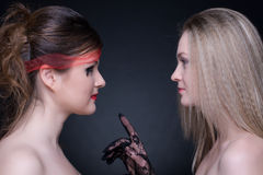 Closeup portrait of two girls: good & evil Stock Images