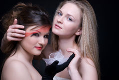 Closeup portrait of two girls: good & evil Royalty Free Stock Photos