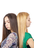 Closeup portrait of two sulky teenage girls standing back to bac Royalty Free Stock Photo