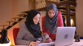 Closeup portrait of two young successful muslim businesswomen discussing the data and graph in front of the laptop then. Looking at camera and smiling stock video