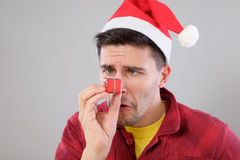 Closeup portrait unhappy, upset man holding small red gift Royalty Free Stock Photography