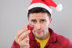 Closeup portrait unhappy, upset man holding small red gift Stock Images
