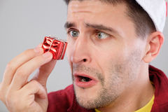 Closeup portrait unhappy, upset man holding small red gift Royalty Free Stock Photo