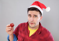 Closeup portrait unhappy, upset man holding small red gift Stock Image